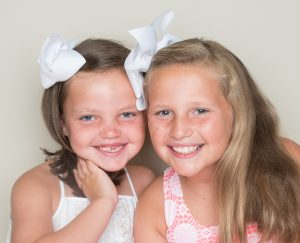 Smiling children with big white bows